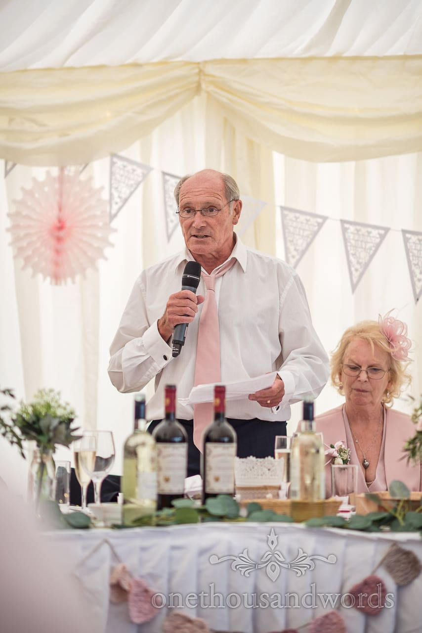 Father of the bride reads his wedding speech with a microphone from behind the top table in wedding marquee photograph