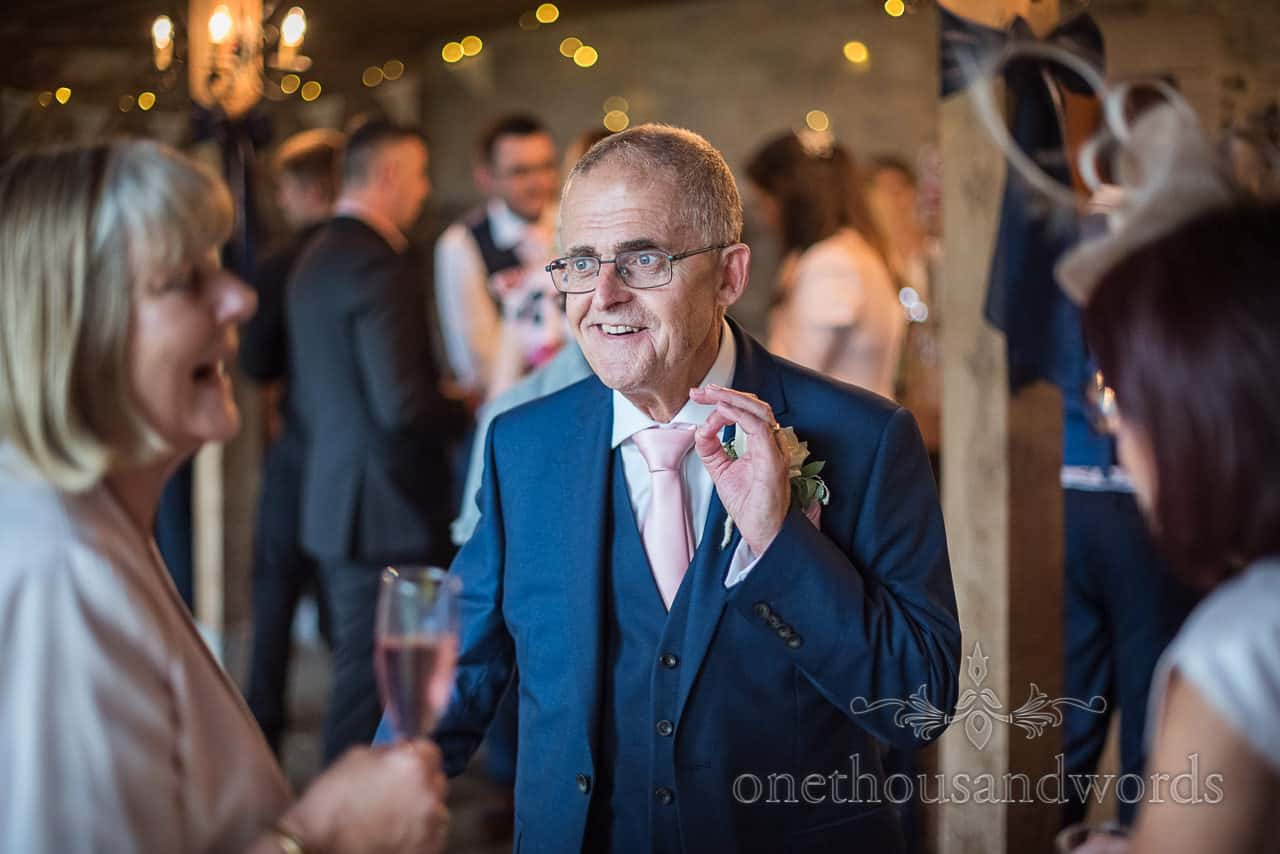 Father of the bride tells a joke at wedding drinks reception at Kingston barn wedding venue in Dorset