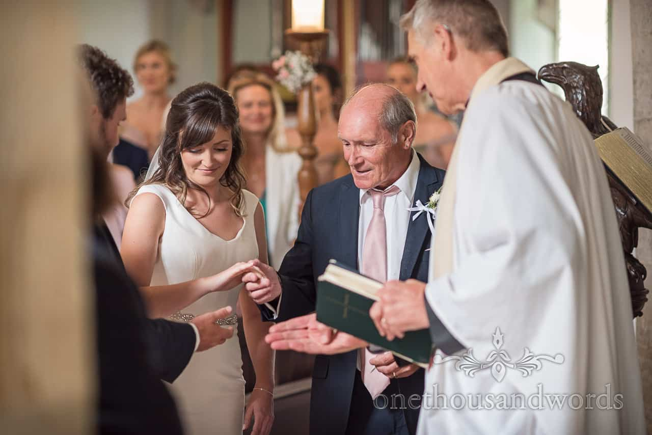 Father of the bride gives her hand in marriage away to the groom during Dorset church wedding ceremony photograph