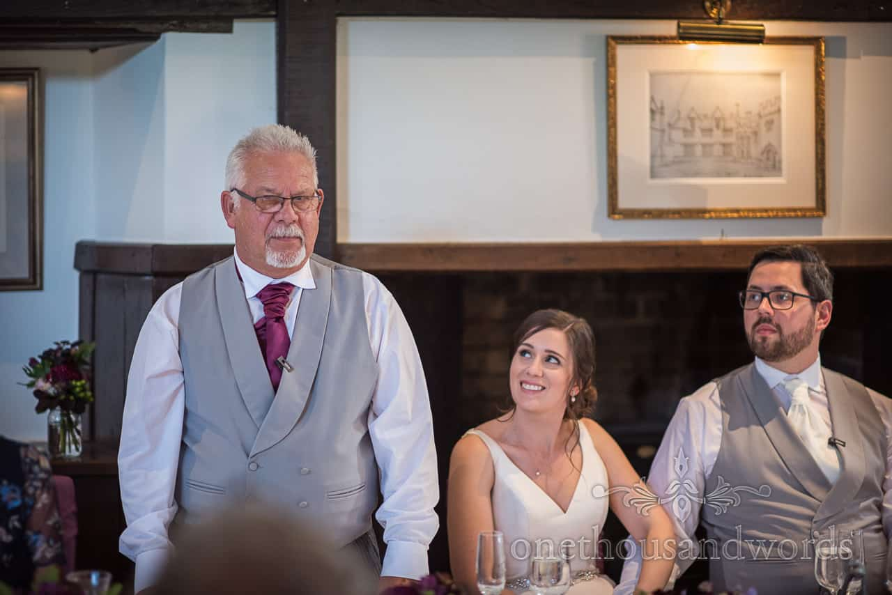 Father of the bride wearing grey waistcoat and purple tie has a serious face during wedding speech as bride laughs