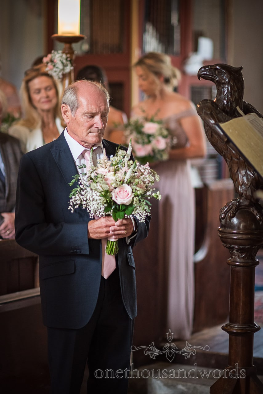 Sombre looking father of the bride holds pink, white and green floral bridal bouquet during church wedding ceremony