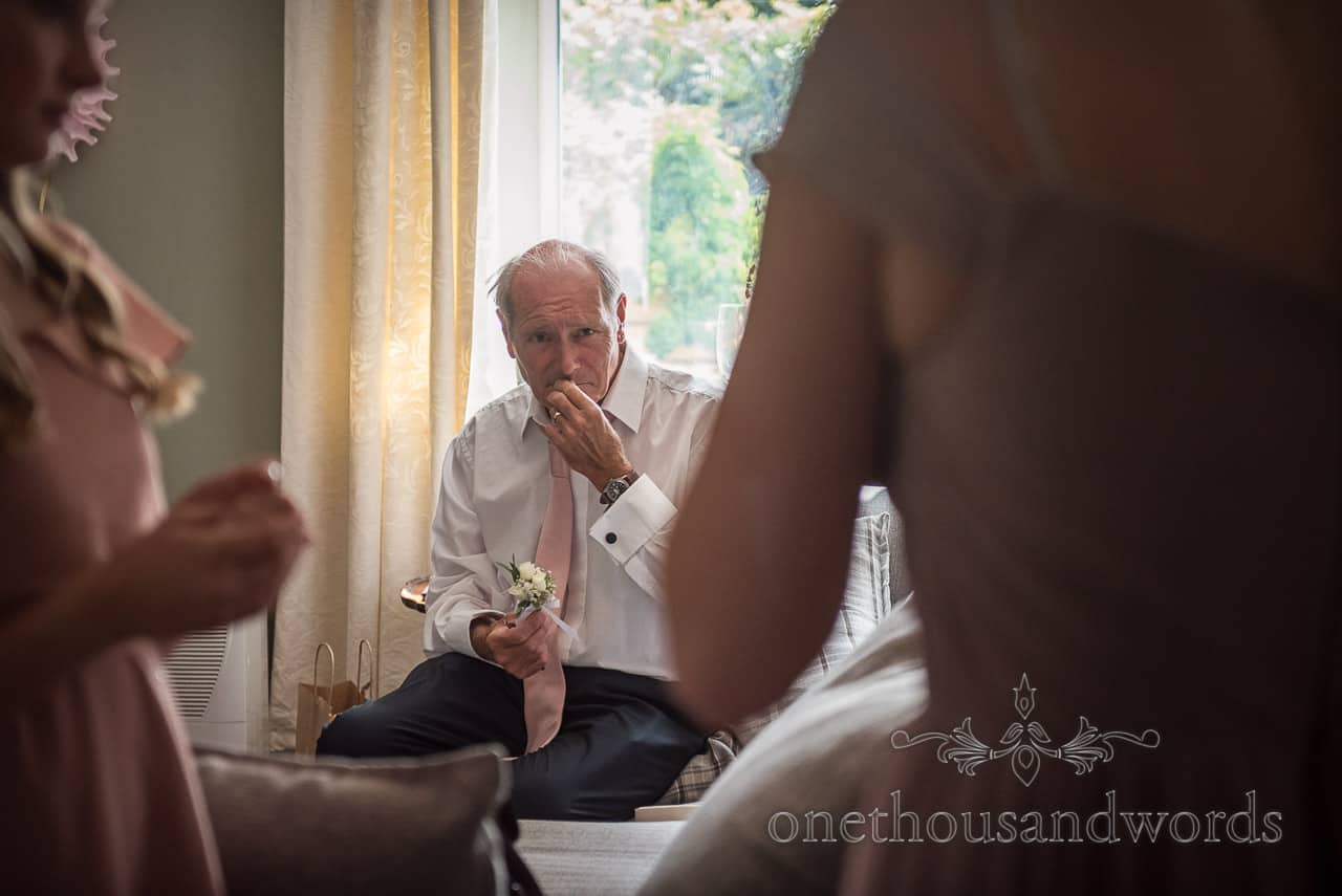 Documentary photo of father of the bride sitting in a window looking emotional on wedding morning with his daughter