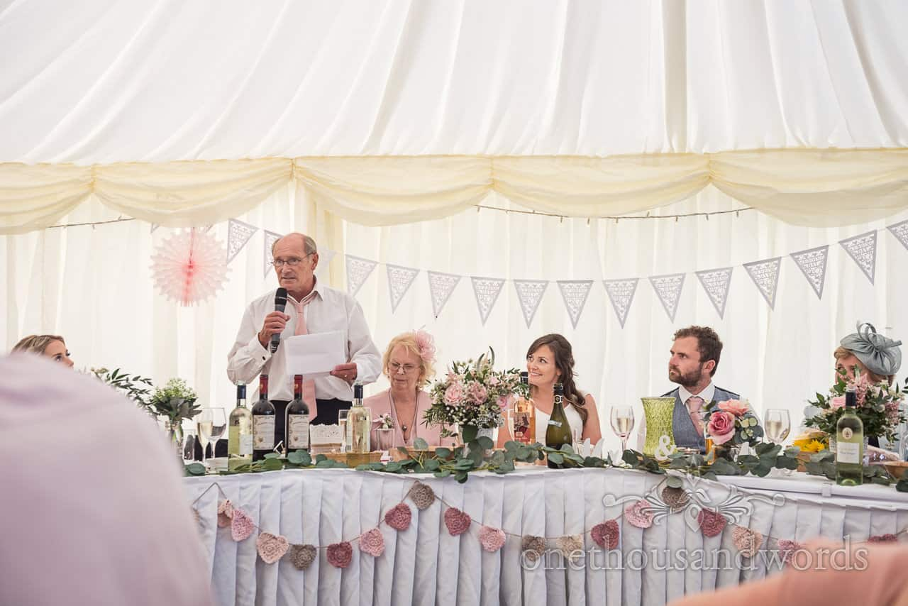 Bride and groom watch father of the bride's speech behind top table at marquee wedding decorated with bunting