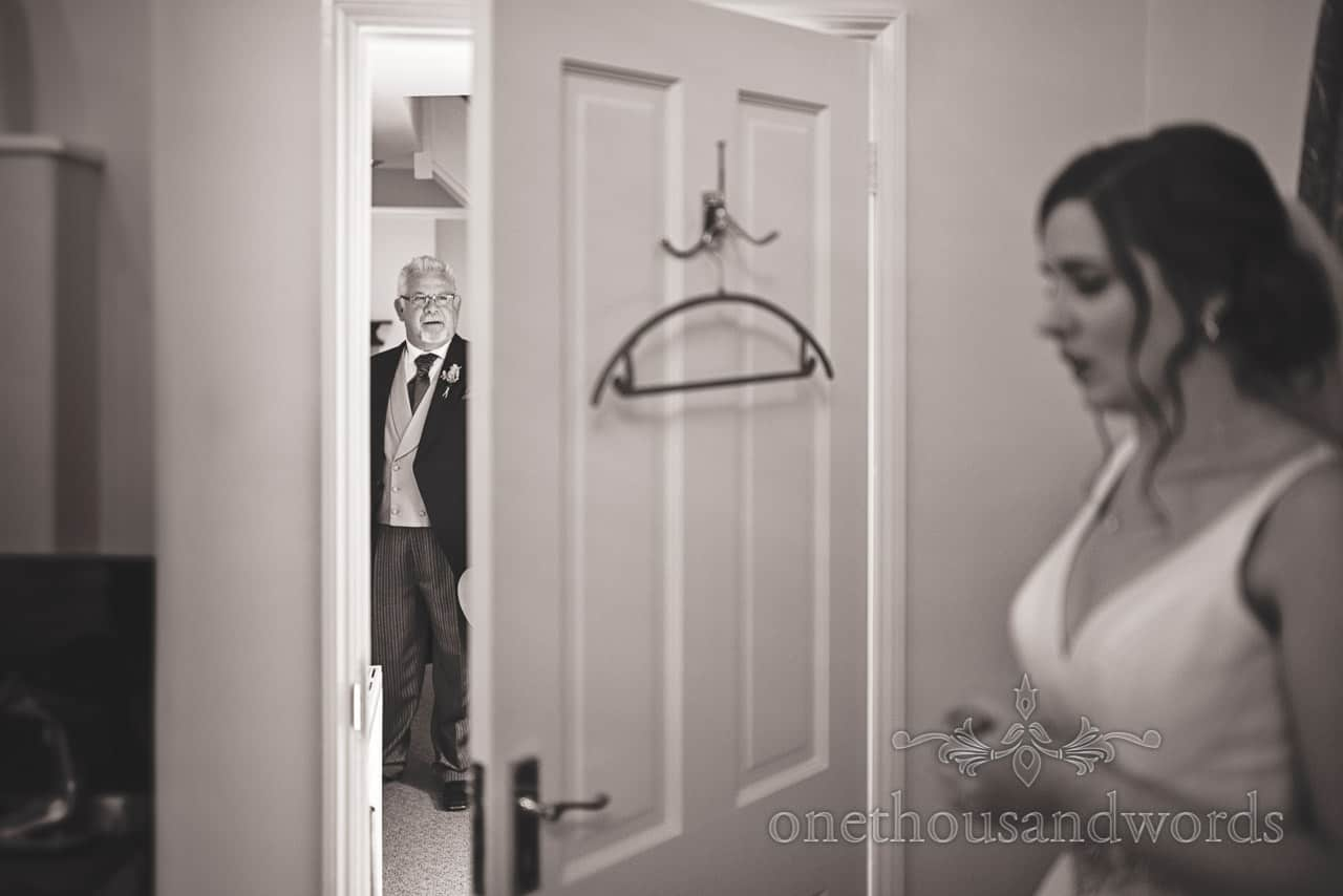 Father of the bride waits through doorway for daughter to show off wedding dress first look on wedding morning photograph