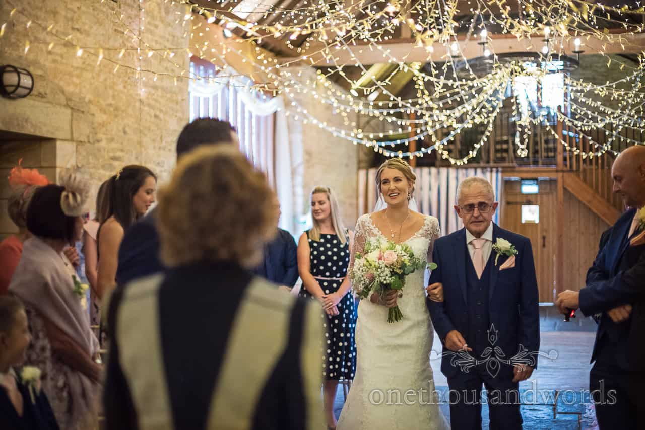 Father escorts bride down aisle under fairy lights at barn wedding venue in Dorset by one thousand words documentary photographers