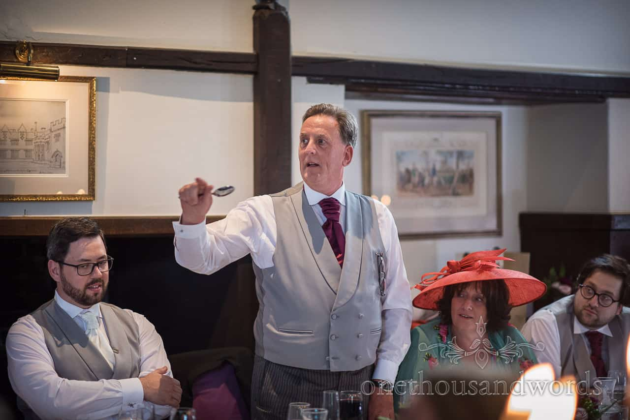 Father of the groom in grey waistcoat acting as Master Of Ceremonies announces wedding speeches with a spoon in hand