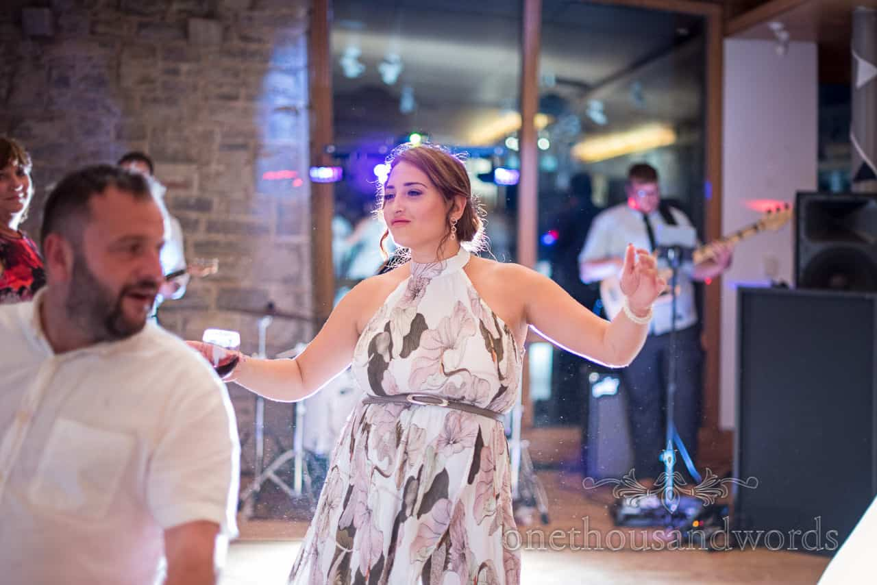 Dancing female wedding guest illuminated by stage lighting on dance floor with wedding band playing evening music
