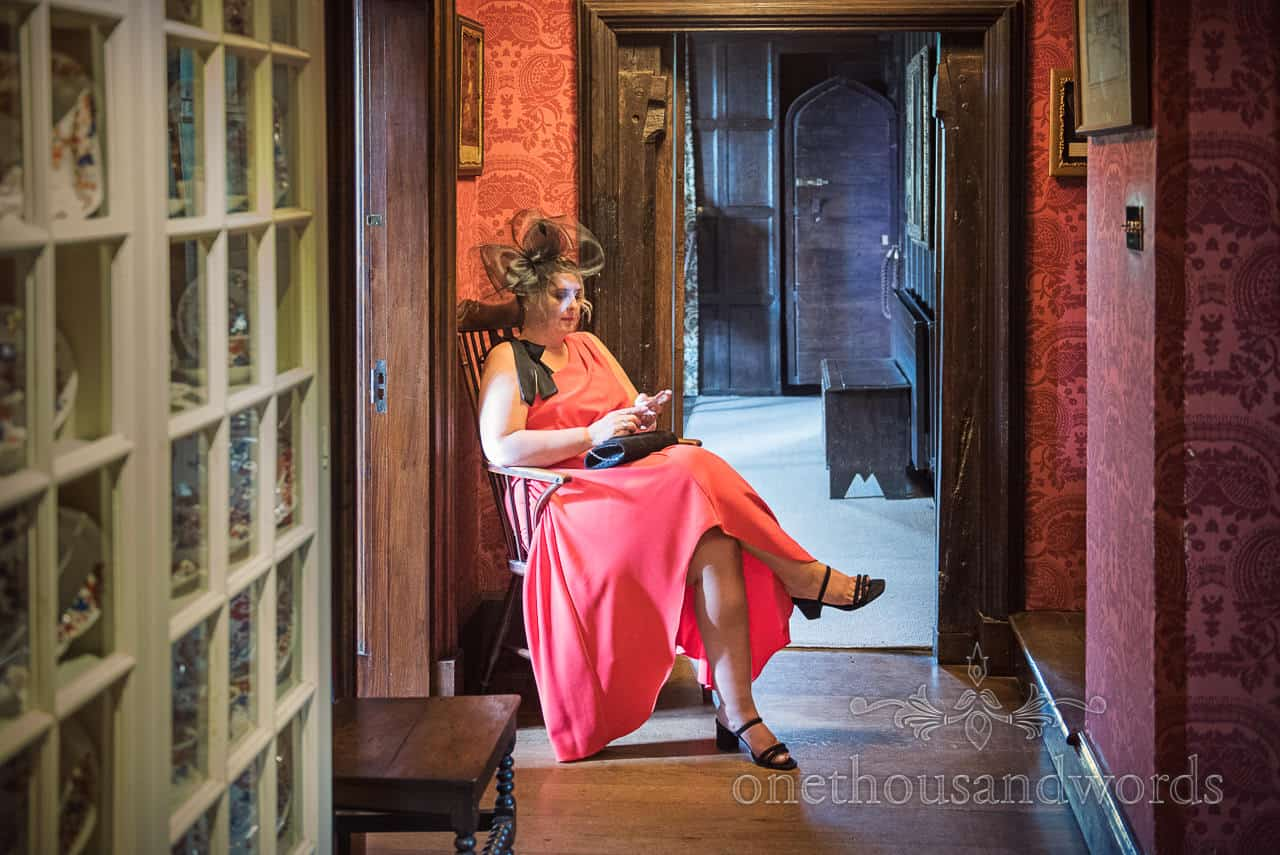 Female wedding guest in red dress sits waiting on wedding morning in Athelhampton House wedding venue in Dorset