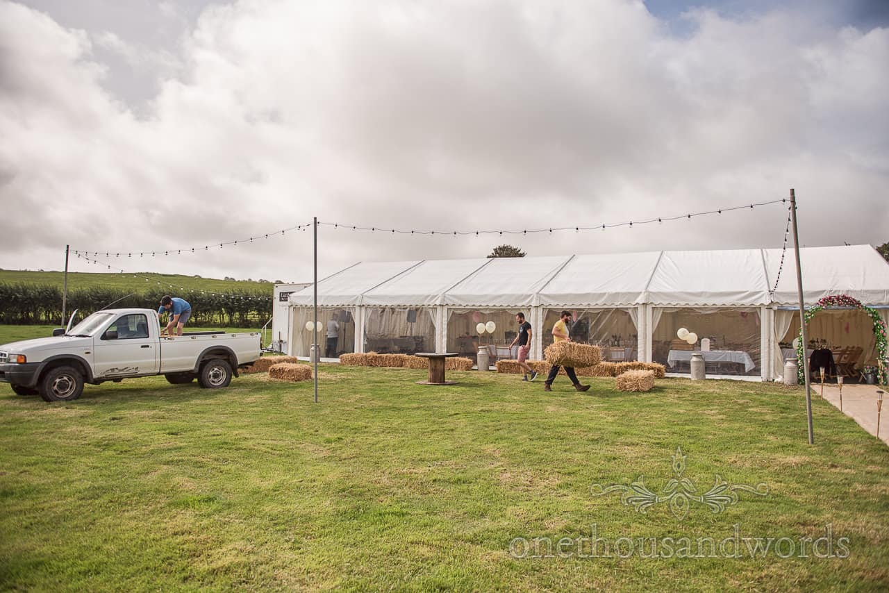 Final site preparations offloading straw bales for Purbeck farm marquee wedding photographs in Dorset countryside field