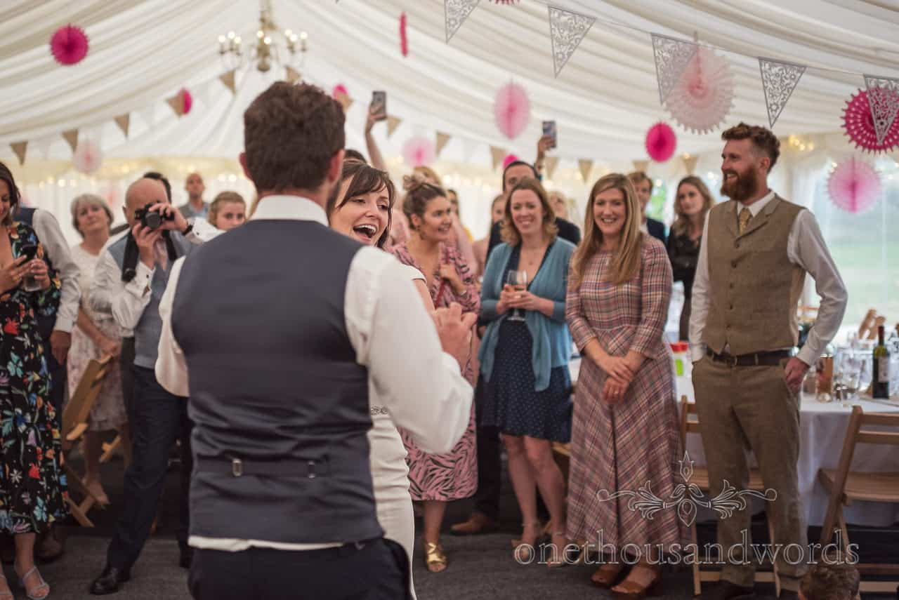 Bride laughs during first dance surrounded by smiling wedding guests at Purbeck farm marquee wedding photographs