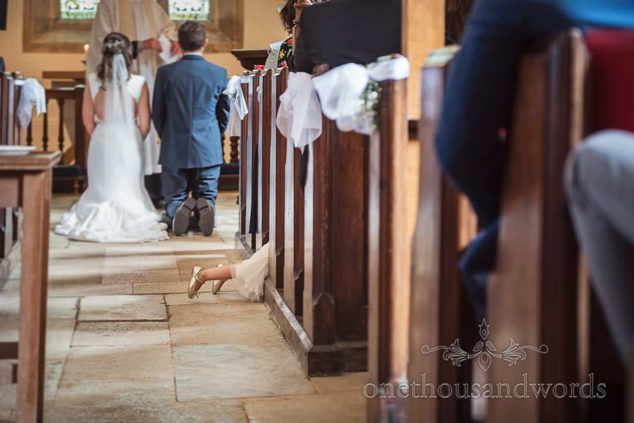 Funny documentary wedding photograph of flower girl lying with feet in the aisle during blessing at Dorset church wedding