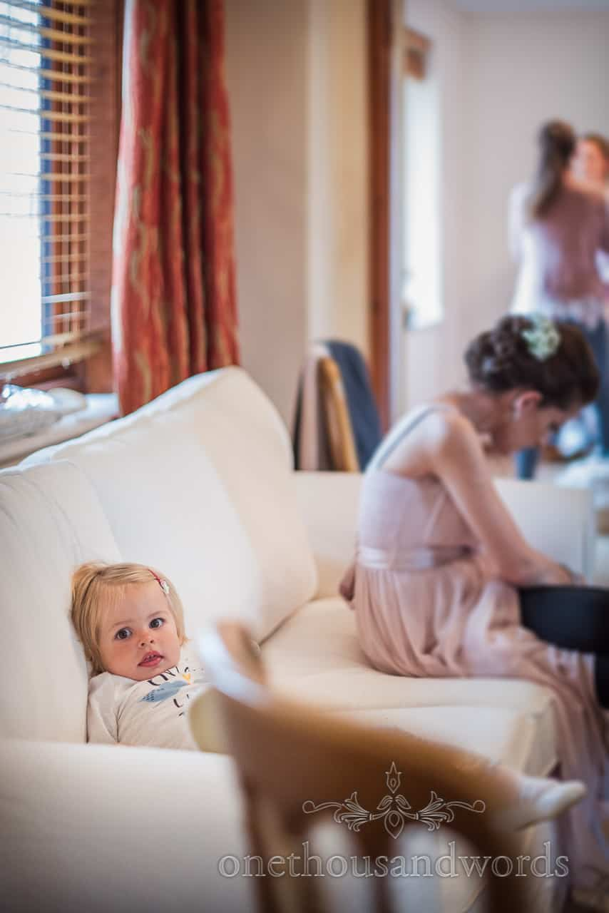 Documentary wedding photograph of flower girl sat on sofa during bridal morning preparations for Dorset wedding