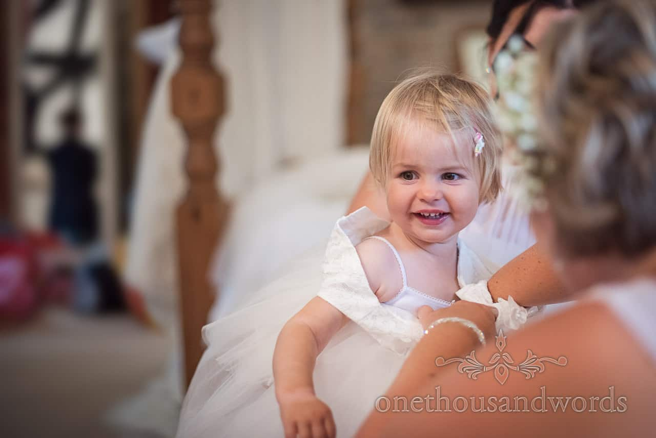 Smiling cute flower girl is helped into small white dress during wedding morning preparations photograph by one thousand words