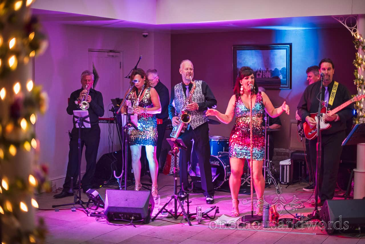 Funky wedding band lit with multicoloured disco lighting performing at Athelhampton Coach House wedding evening reception