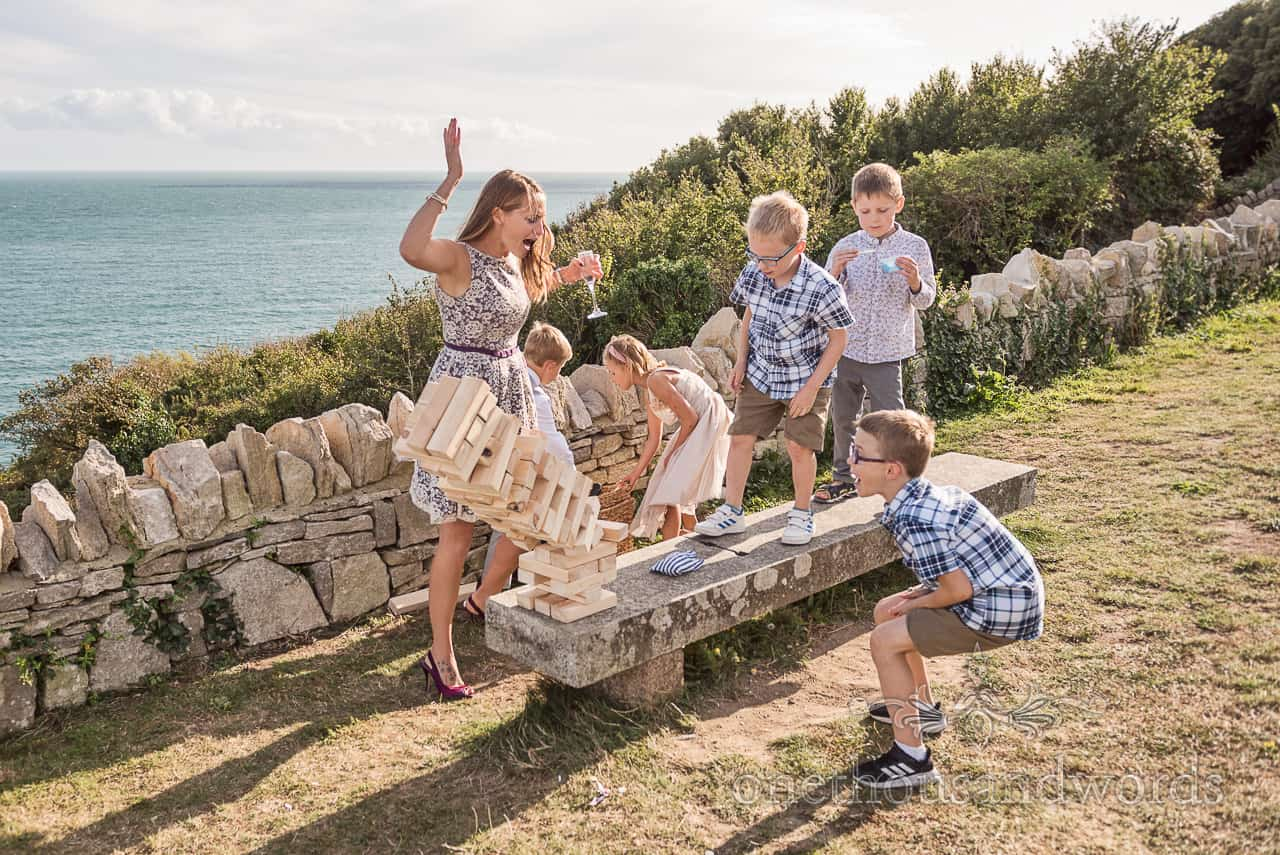 Giant Jenga wedding garden games in the summer sunshine on the Dorset coast with sea views by one thousand words