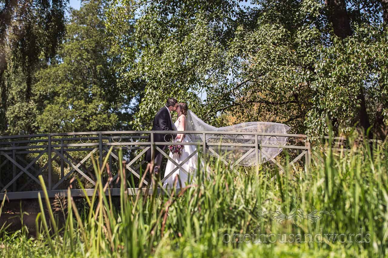 Wedding couple photograph of groom and bride with veil blowing in the wind stood on a bridge over a river in the Dorset countryside
