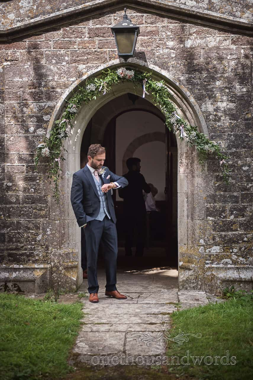 Groom in three piece blue suit checks his watch outside Dorset stone Church doorway whilst waiting to greet wedding guests