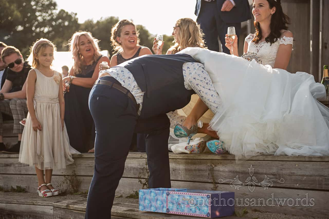 Wedding guests backlit with low sun watch as groom climbs under bride's wedding dress to put on her bridal wedding shoes