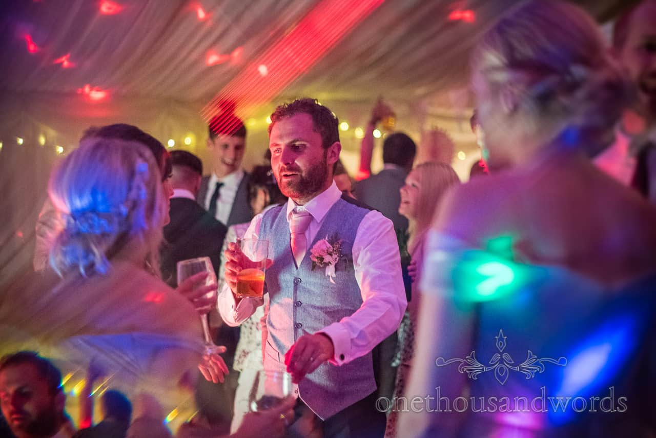 Groom dances under multi colour disco lights with drink in hand in wedding marquee photograph by one thousand words photography