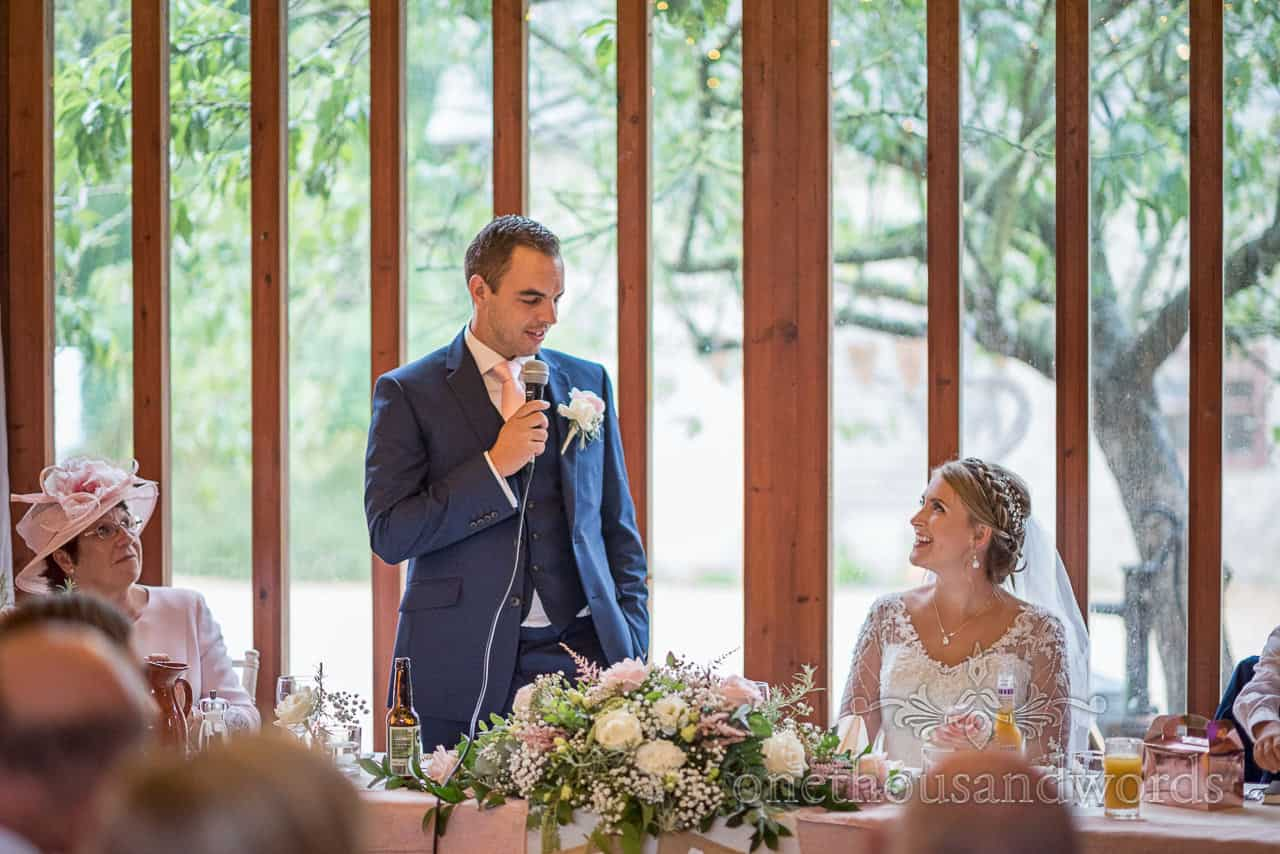 Groom delivers wedding speech with microphone behind top table against window at Kingston barn wedding in Dorset
