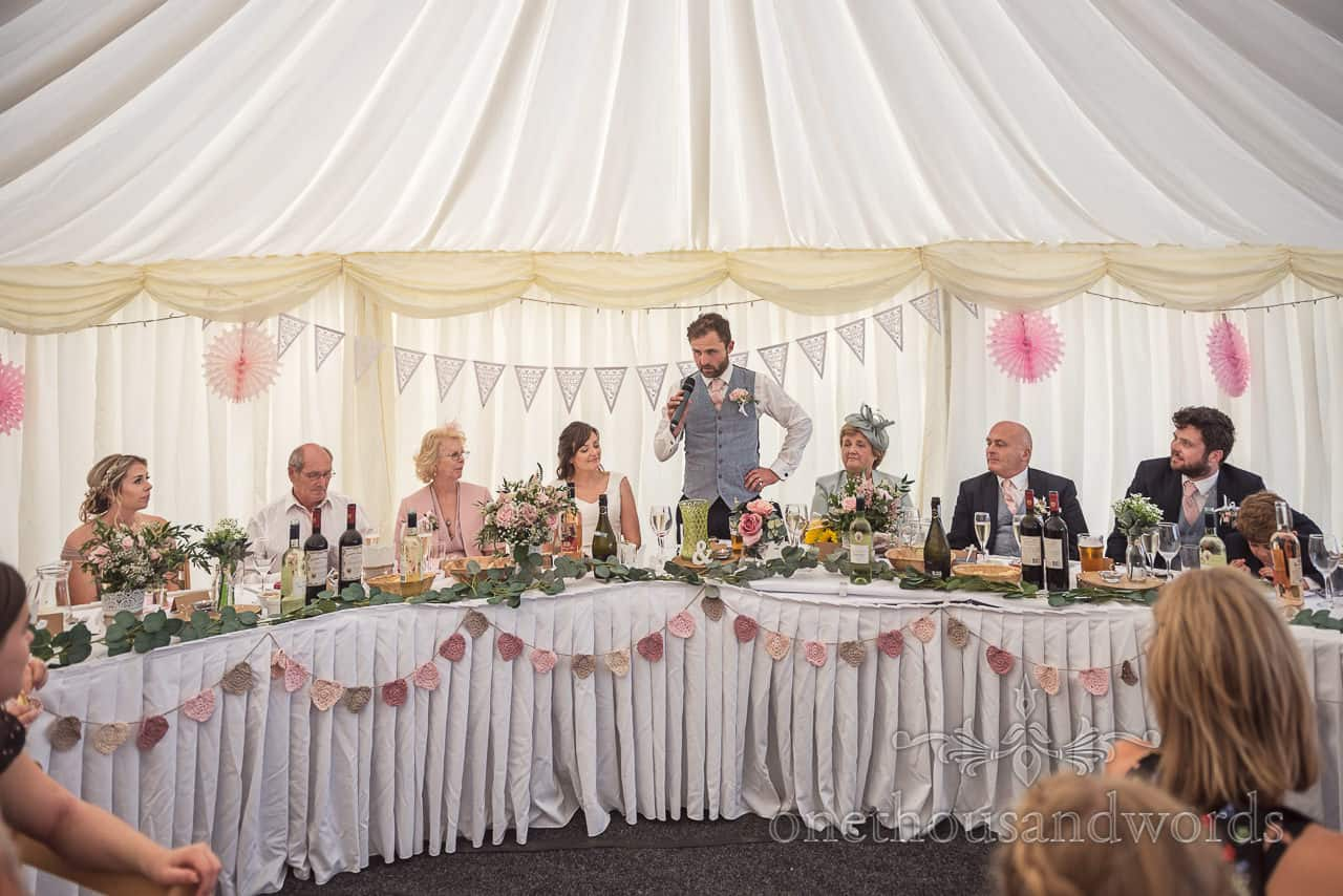 Groom delivers wedding speech from curved top table decorated with bunting at Purbeck farm marquee wedding photographs