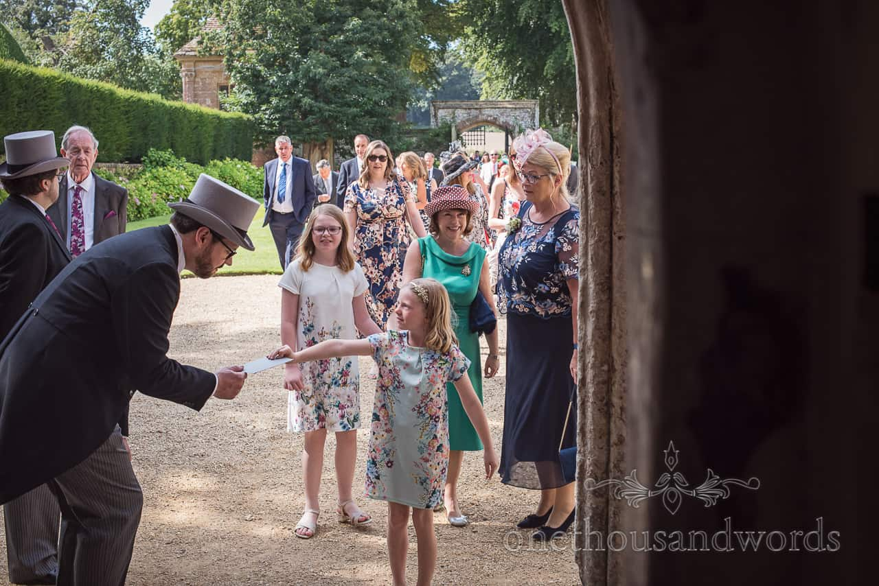 Groom greets wedding guests in doorway at Athelhampton wedding photographs by one thousand words wedding photography Dorset