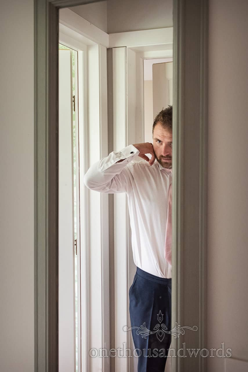 Documentary wedding photograph of groom adjusting shirt collar in mirror on wedding morning by one thousand words photography