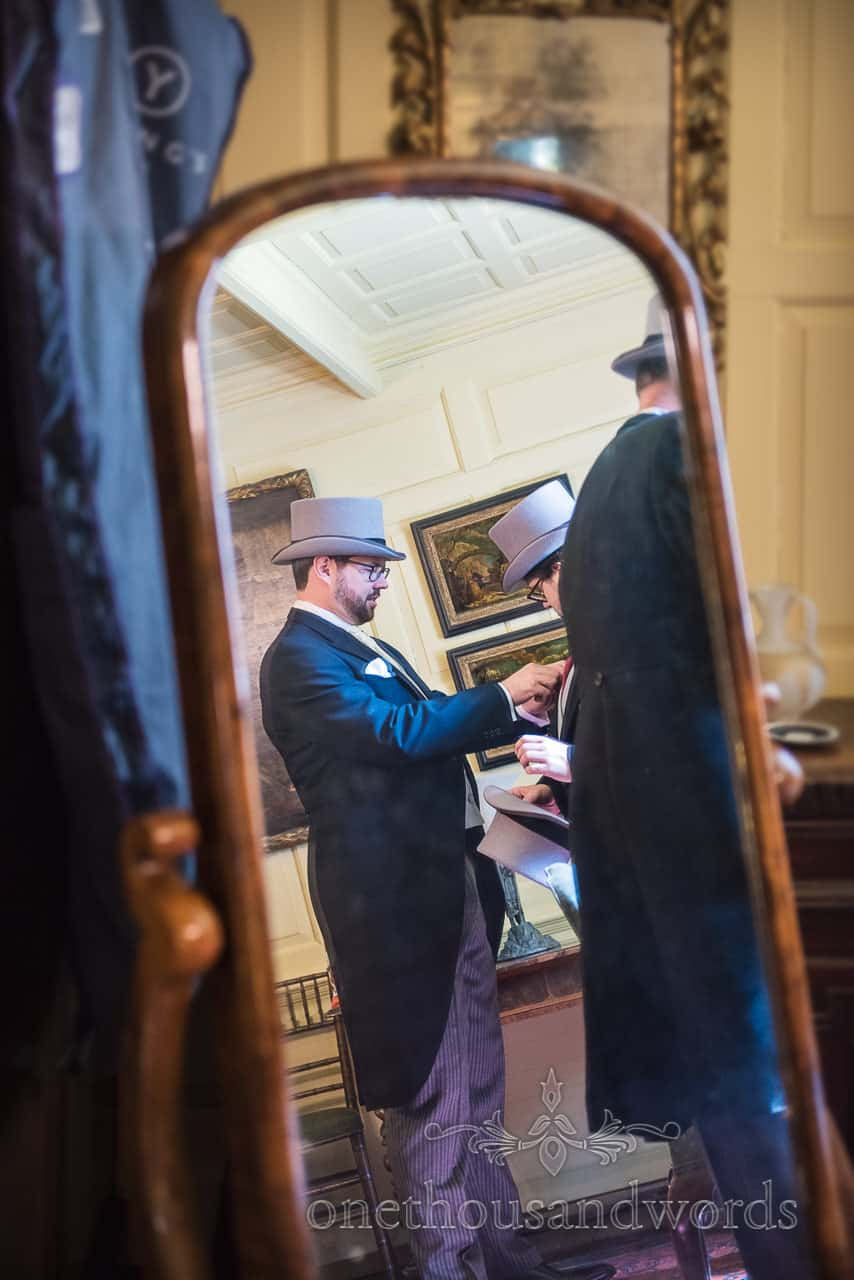 Groom preparation with grey top hats and black and grey tail suits taken in mirror reflection photo by one thousand words photography