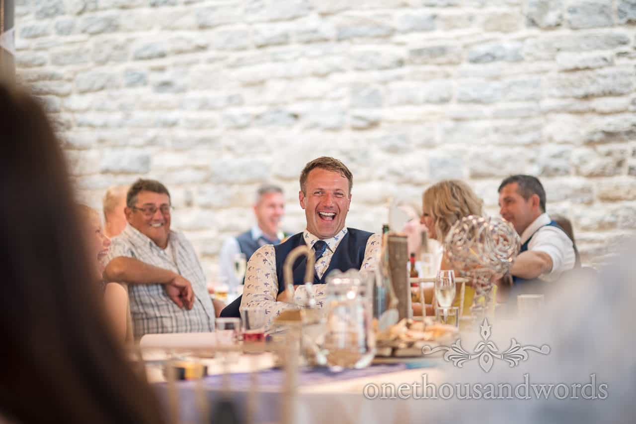 Grooms laughing reaction to best man's wedding speech in Purbeck stone castle wedding venue by one thousand words photographers