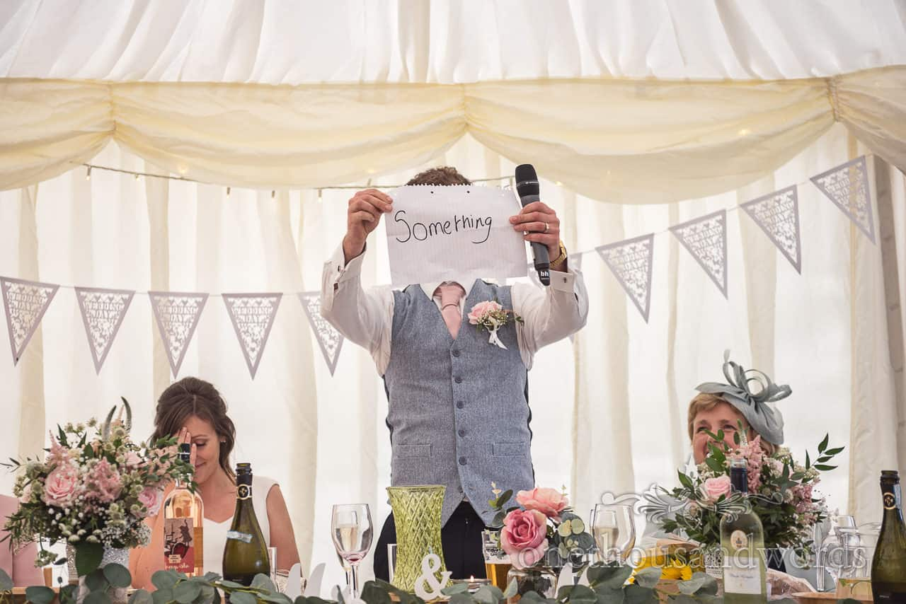 Bride holds her head in hands as groom shows that he wrote the word something during wedding speeches in a marquee