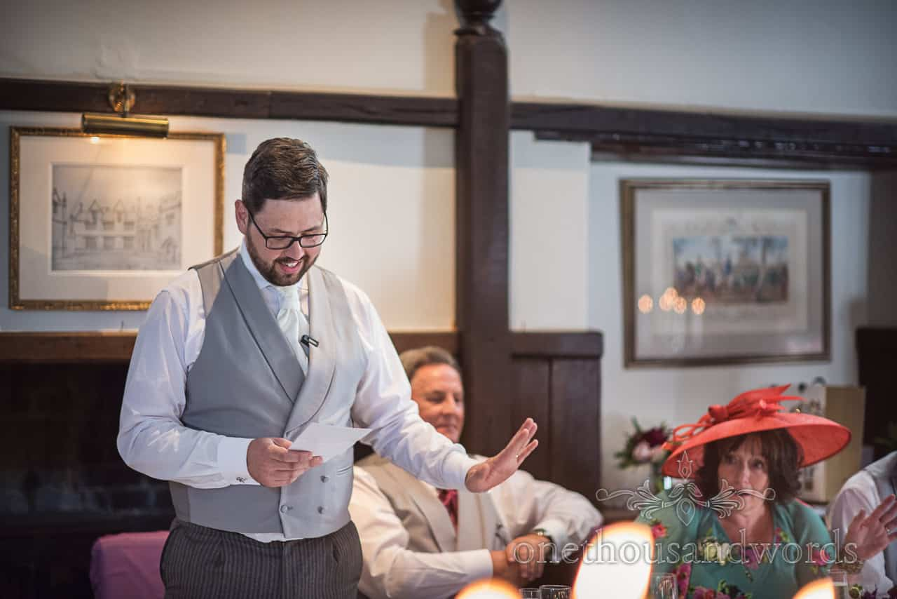 Documentary wedding photograph of groom in grey waistcoat silencing mother of bride with his hand during wedding speech