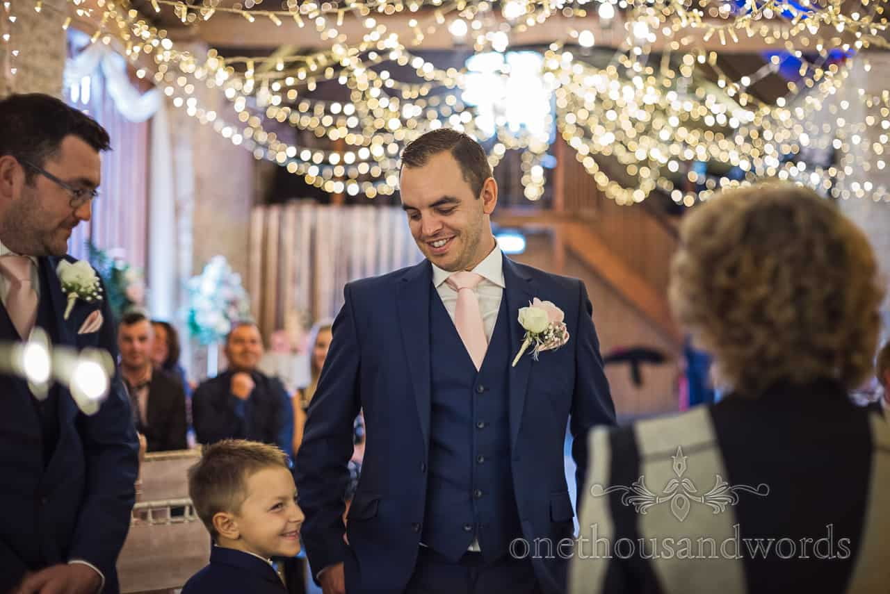 Groom and page boy son share a joke under fairy lights decorations before Dorset barn wedding ceremony by one thousand words