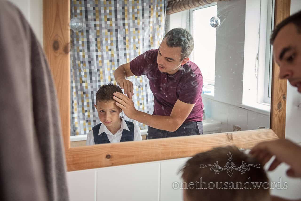 Documentary wedding photograph of groom and son style hair in mirror on wedding morning by one thousand words photographers