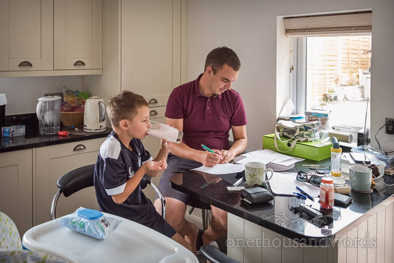Documentary wedding photograph of groom writing wedding speech with son at breakfast table on wedding morning in Dorset
