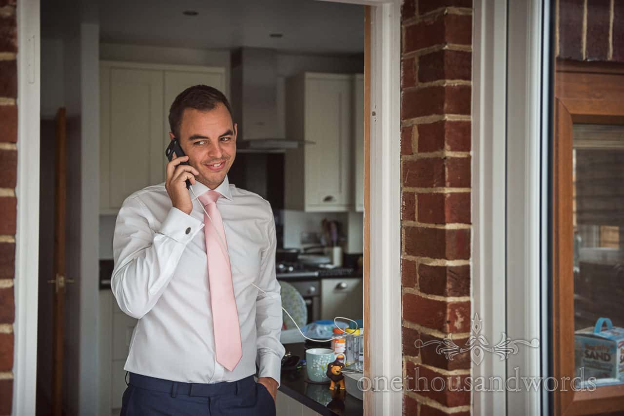 Groom makes phone call during wedding morning preparations at home in Dorset by one thousand words documentary photography