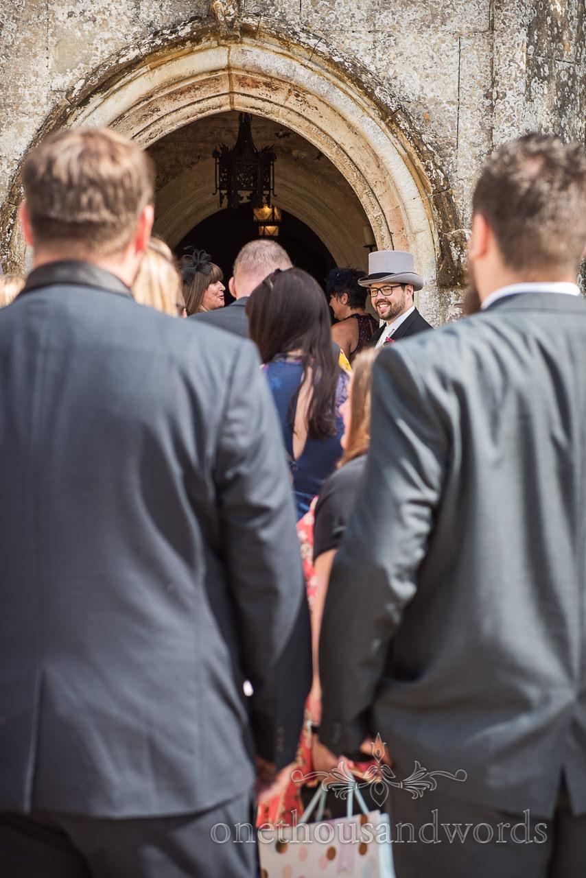 Groom in grey top hat greeting arriving wedding guests at Athelhampton House wedding venue