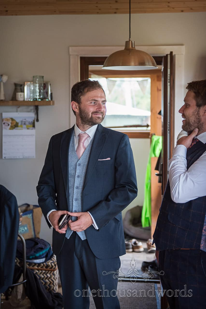 Groom wears three piece blue wedding suit during wedding morning preparations in wooden cabin on Purbeck farm