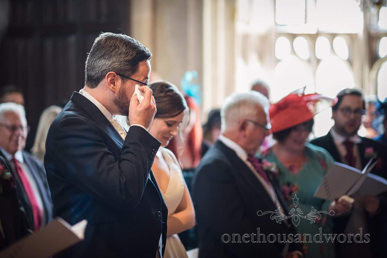 Groom wipes tears from his eyes whilst crying during Athelhampton House wedding ceremony photograph by one thousand words