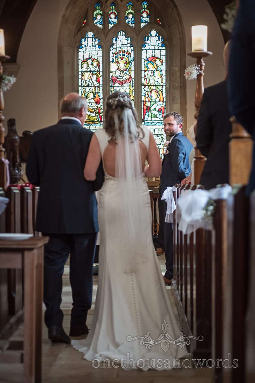 Grooms first look at bride down the aisle at Dorset church wedding ceremony photographs by one thousand words wedding photography