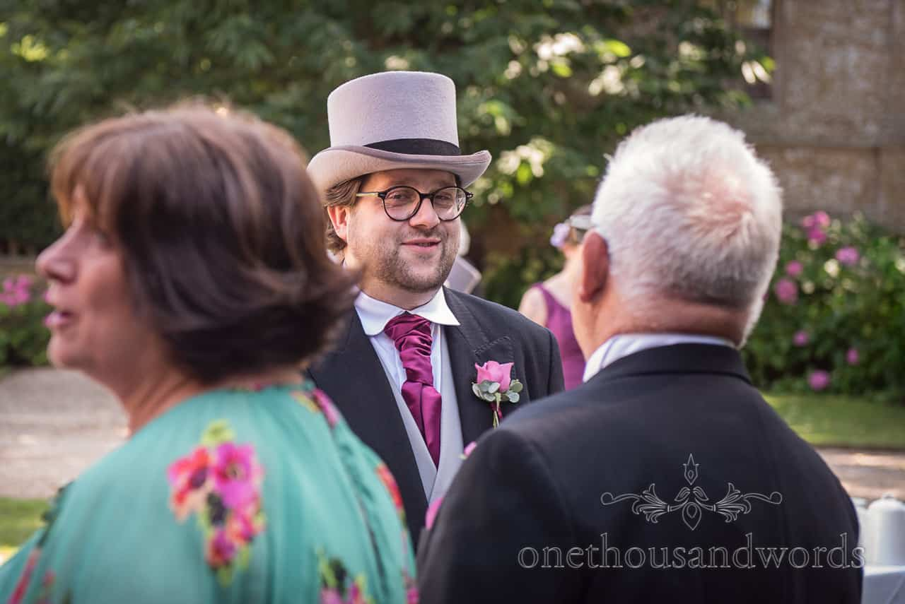Wedding portrait photograph of grooms man in grey top hat and purple tie smiling in wedding greeting line