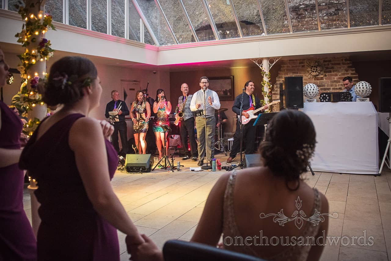 Grooms surprise song performance for seated bride with wedding band at Athelhampton House wedding venue evening reception