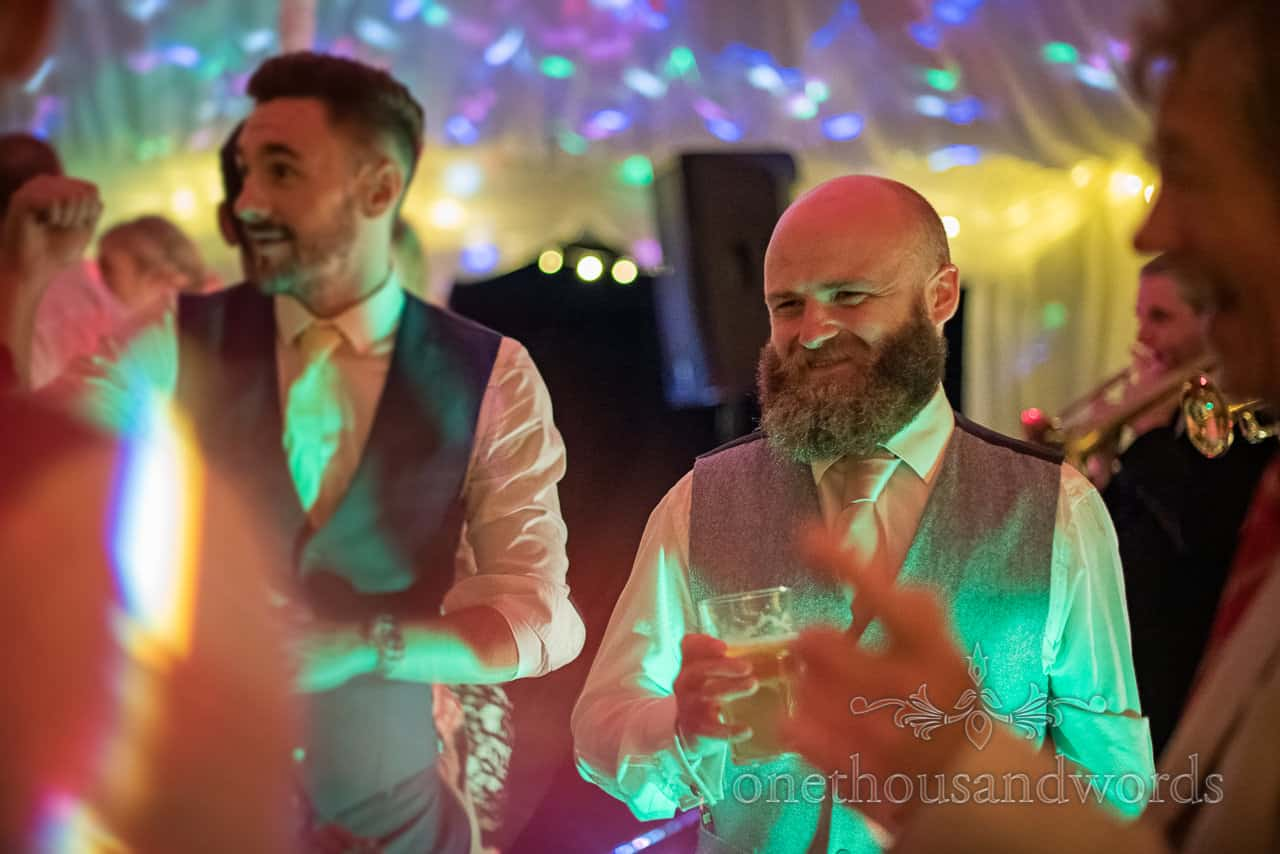 Smiling bearded grooms man in grey waist coat dances with pint in hand under disco lights in wedding marquee photograph