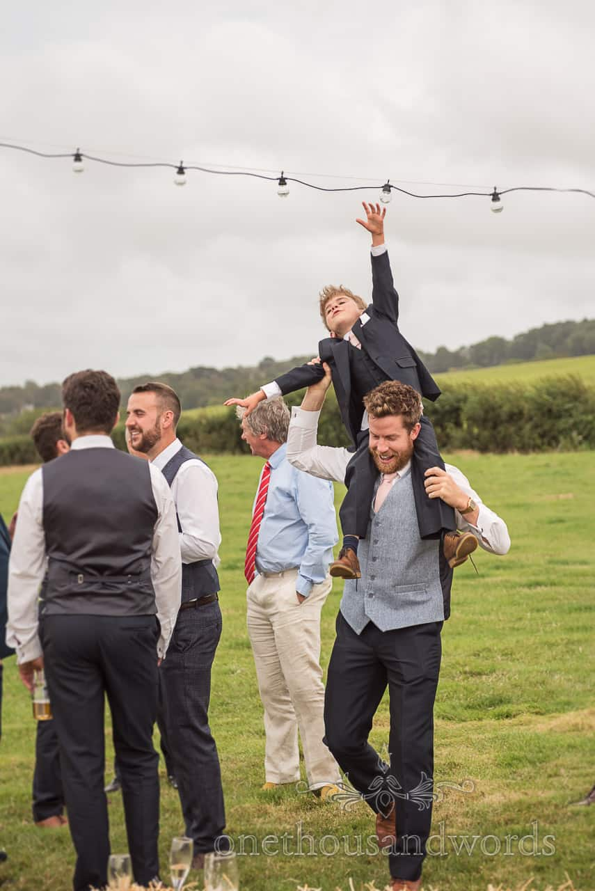 Groomsman carries page boy on his shoulders under festoon lighting through wedding drinks reception in Dorset countryside field