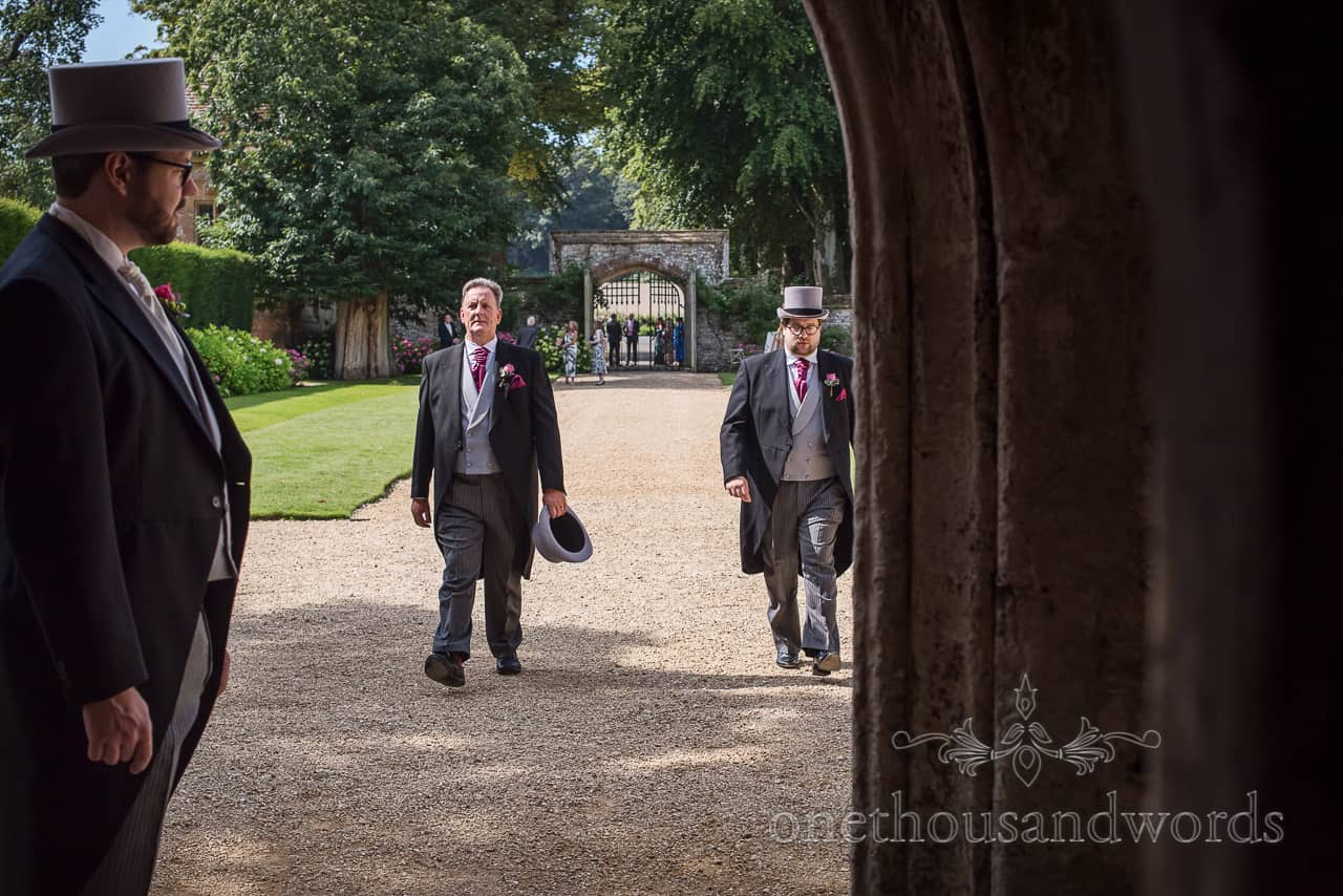 Groomsmen in grey top hats and black morning tail suits arrive at Athelhampton wedding venue documentary photograph