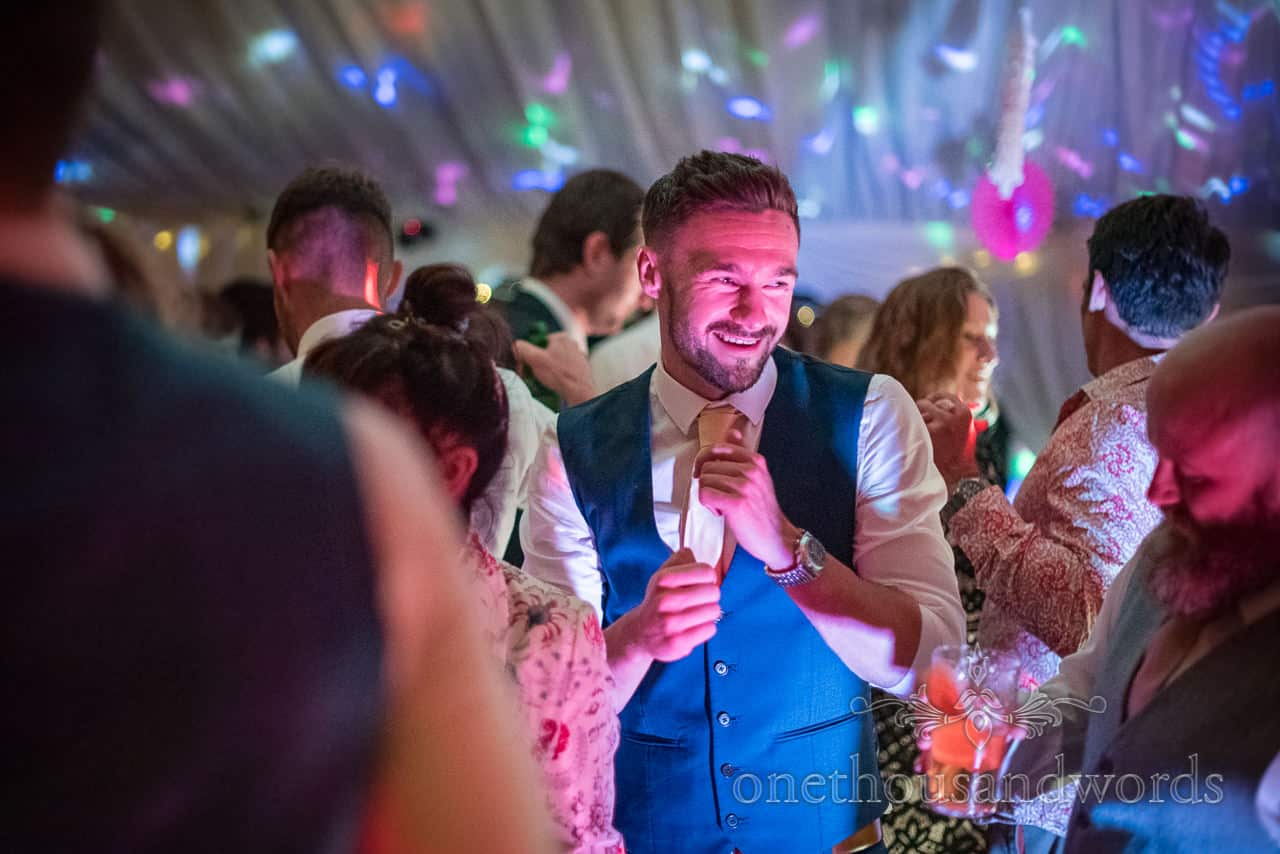 Happy wedding guest in blue waistcoat dances under multi coloured disco lighting in wedding marquee