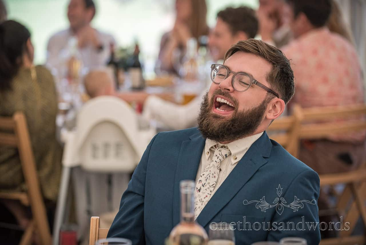 Documentary wedding photograph of bearded wedding guest in blue suit with white patterned tie belly laughing to wedding speeches