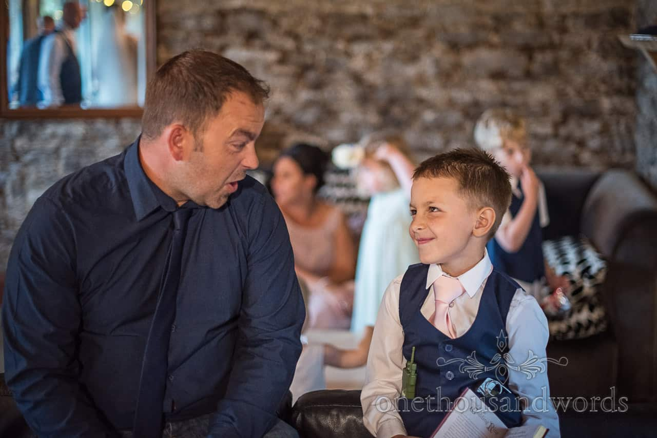 Guest and newly wed's son share funny faces and joke during drinks reception at Dorset barn wedding by one thousand words