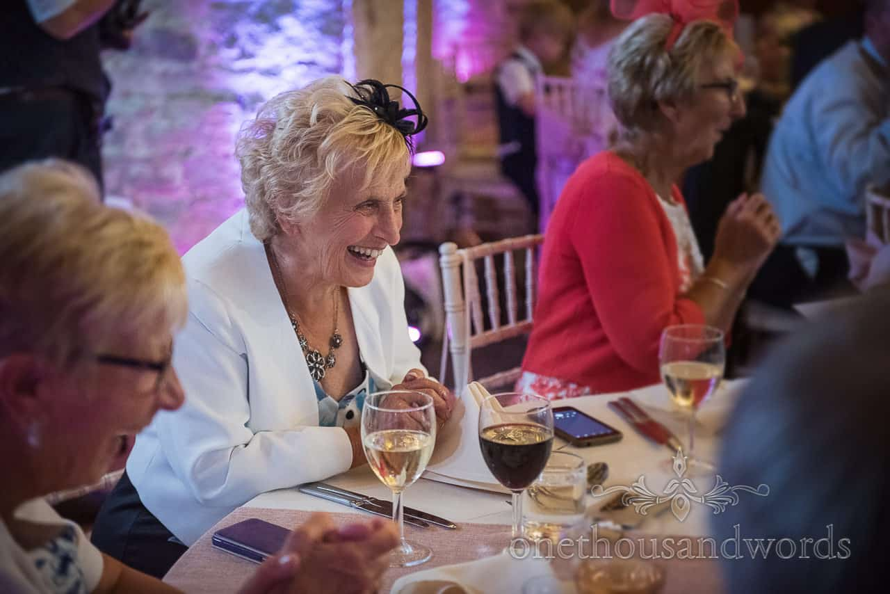 Elderly wedding guest's laughing reaction to cheeky wedding speech by newly wed's son by one thousand words wedding photography