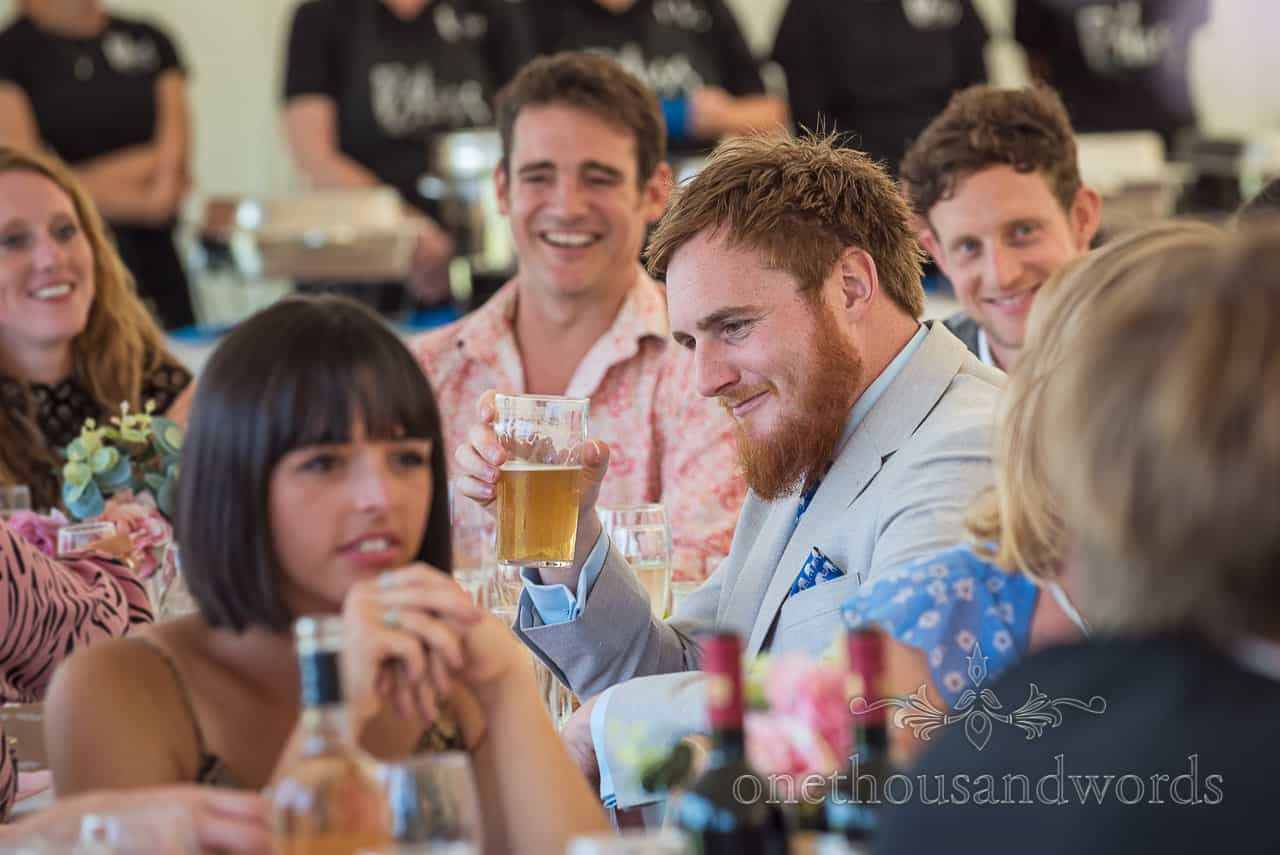 Documentary wedding portrait photograph of wedding guest raising his pint of beer as a reaction to wedding speeches