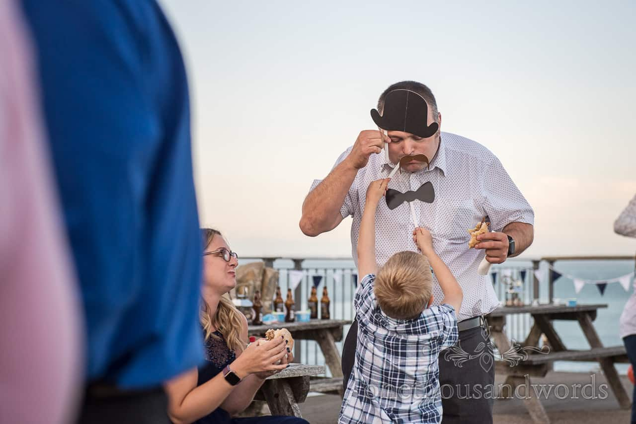 Wedding guest's son plays with photo booth props at Purbeck Castle wedding venue drinks ceremony by one thousand words